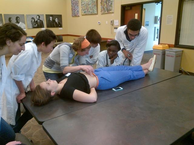 Percussing a patient's abdomen.