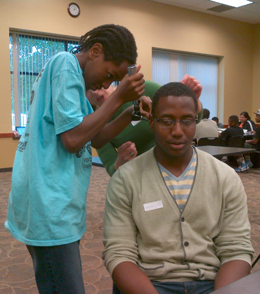 Medical scholar Christopher demonstrating use of an otoscope